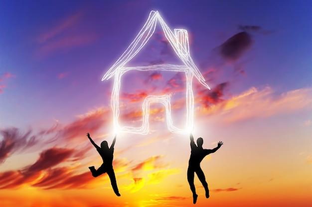 Люди прыжки на закате с домом