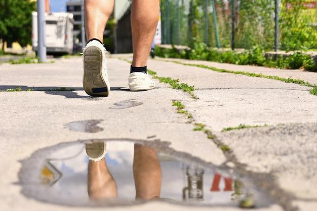 Ноги во время ходьбы. отражения в воде на тротуаре.
