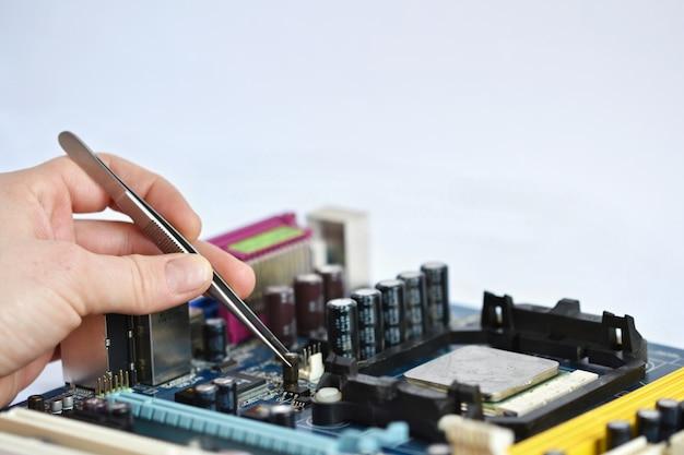 ペンチでチップを配置する技術者