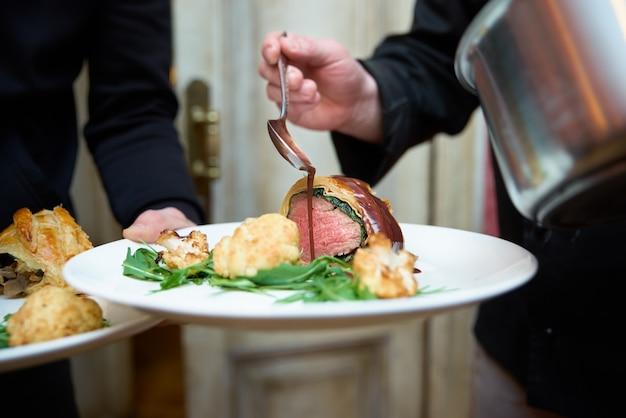 ウェイターの手にあるプレート。オーブンで焼いたカリフラワーと牛ヒレ肉。