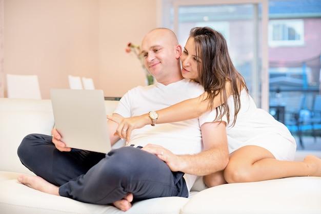 Молодые пары ослабляя на софе с компьтер-книжкой. концепция влюбленности, счастья, людей и потехи.