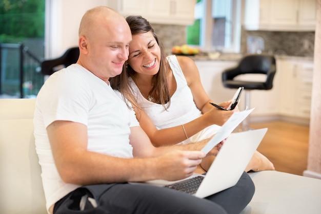 Молодая пара на диване с ноутбуком и рассчитывать счет для оплаты. семейная концепция, семейный бюджет