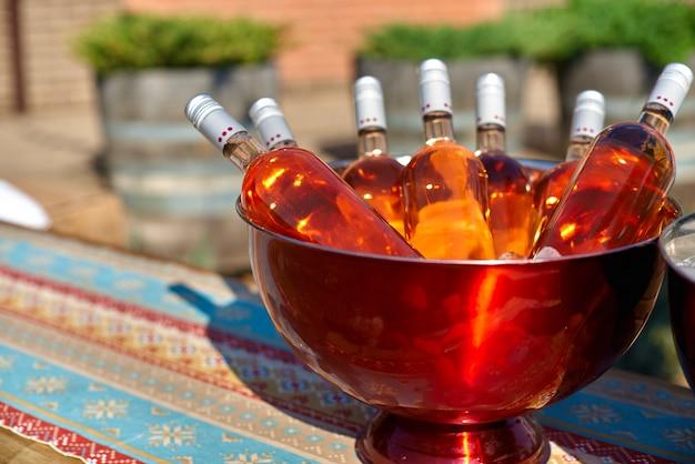 テーブルの上の氷の入ったバケツにピンクワインのボトル。