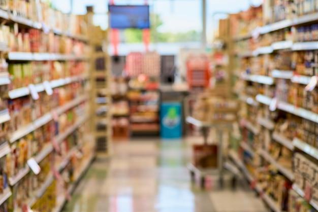 Расплывчатая текстура предпосылки междурядья между полками заполнила с товарами в окружающей среде супермаркета.