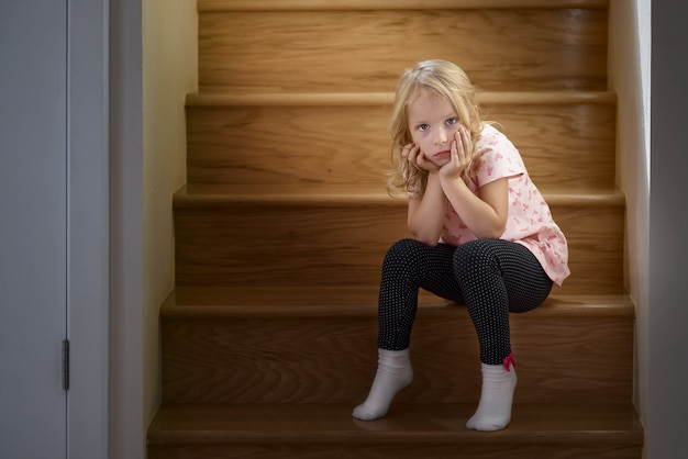 Маленькая девочка сидит на лестнице на второй этаж дома, ждет своих родителей в одиночестве. солнечный свет из окна горит. концепция семьи, детство