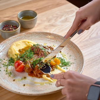 モダンなデザインプレートのクローズアップとしてマッシュルームとマッシュポテトのブラウンソースで煮込んだ牛のほほ肉