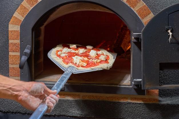 Концепция питания. готовим традиционную итальянскую пиццу. пицца в передней части духовки.
