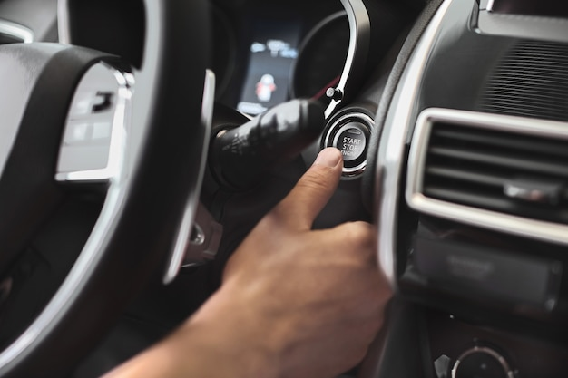 車のエンジンスタートストップボタンを押す指