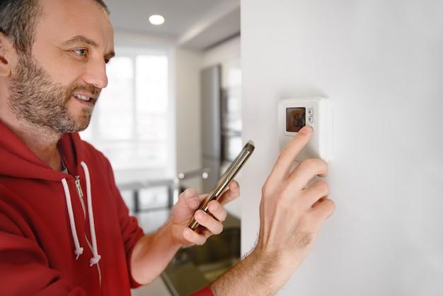 Радостный человек смотрит на свой смартфон, как регулируется температура обогревателя в умном доме
