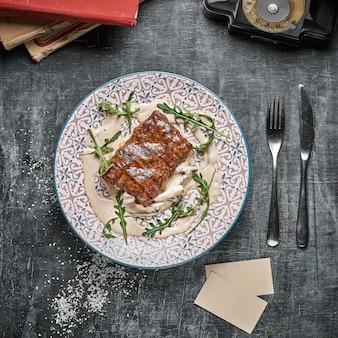 コンセプト:レストランメニュー、健康食品、自家製、グルメ、大食い。風化した木製のテーブルにステーキとキノコのソースとプレート。トップダウンビュー