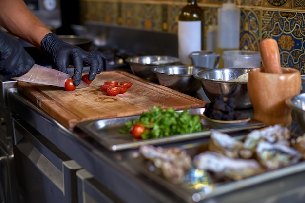 シェフはトマトを切って、キッチンのテーブルで料理の材料を準備します。