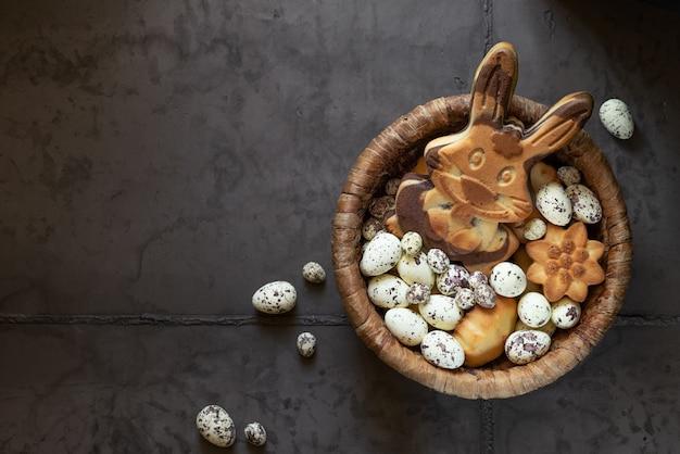 灰色のコンクリートの背景にイースタージンジャーブレッドクッキー。ジンジャーブレッドのような卵とウサギ。挨拶用のスペースがある上面図