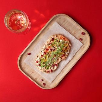 木の板にフムスアボカドサンドイッチ。ライ麦パン、フムス、ザクロの種子のサンドイッチ。家族全員のための健康的な食事