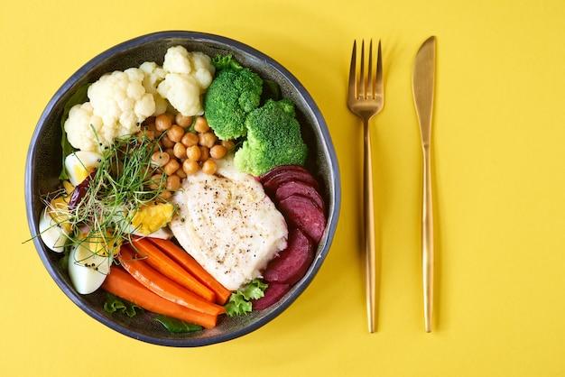 揚げタラの切り身と野菜:にんじん、芽キャベツ、ブロッコリー、カリフラワー、トウモロコシのサラダ。健康食品。セレクティブフォーカス