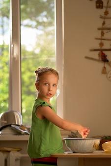 かわいい女の子が台所で料理をしています。クッキー作りをお楽しみください。彼女が撮影された驚いた表情