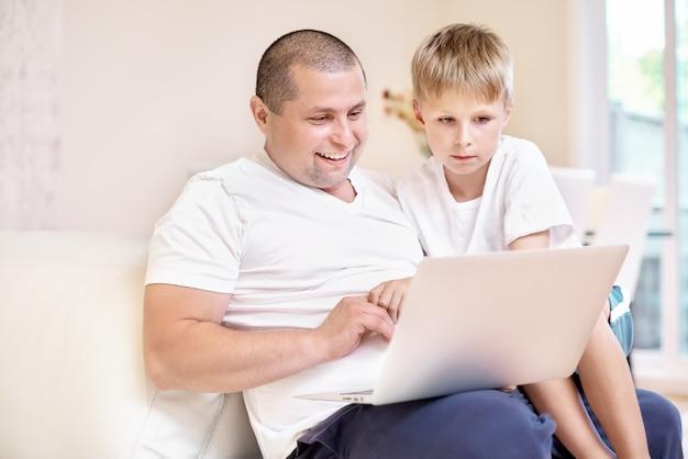 Сын и его отец сидят на диване, глядя на ноутбук, счастливые эмоции от увиденного, счастливая семья