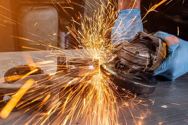 Крупный план по бокам разлетаются яркие искры от угловой машины. молодой сварщик-мужчина в белых рабочих перчатках в гараже шлифует металлическое изделие угловой машиной