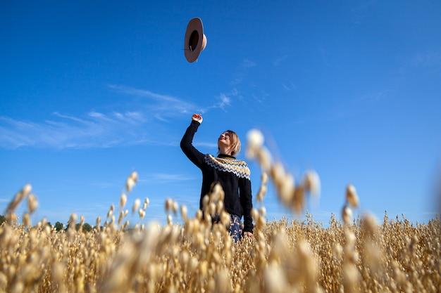 Портрет открытый атмосферный образ жизни фото молодой красивой темноволосой женщины в коричневый вязаный свитер, платье бросает шляпу в небо на фоне поля пшеницы. осенняя прогулка