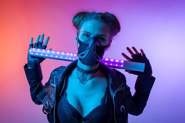 デザインアートのコンセプトです。創造的なカラフルな明るいネオンの肖像画。 。防護マスクの女性の映画の夜の肖像画はランプを保持します