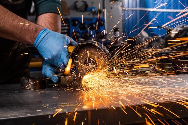 Молодой человек сварщик точильщик металла угловая шлифовальная машина в мастерской, искры летят в сторону. сварщик работает на заводе с металлом