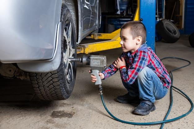 ガソリンスタンドのガレージにある空気レンチを使って、若い自動車労働者の少年がタイヤを交換します。子供は、自動車修理サービスで力学を変える職業を学びます。