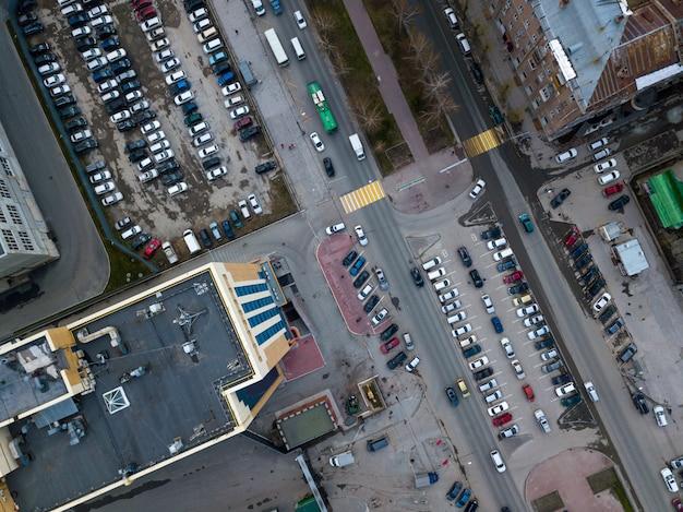 ヘリコプタードローンショット。ある地域、大きな交差点、駐車場、高層ビル、公園、道路などの近代都市の航空写真。上から撮影したパノラマ都市