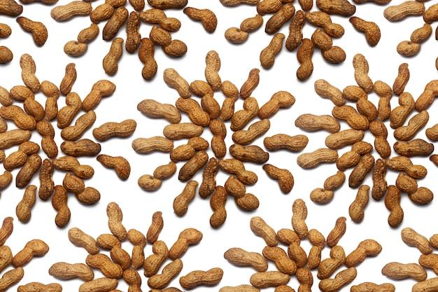 Собрание нерафинированных арахисовых орехов лежит в форме круга или солнца на изолированной белой стене. сырой арахисовый образец