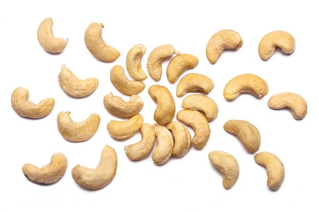 Ореховый узор - кешью на белой стене в форме круга. понятия об украшении, здоровом питании и пищевой стене.