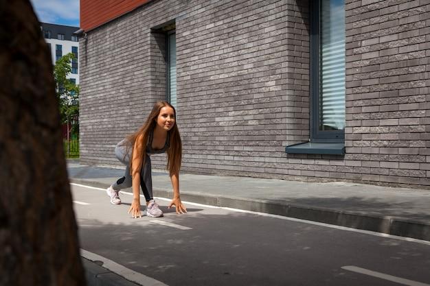 Гимнастка молодой женщины с стройной фигурой в спортивной одежде делает растяжки на улице города в теплый летний день. растяжка на открытом воздухе