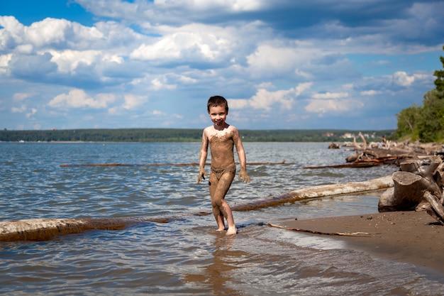 Веселый маленький мальчик наслаждается летом и играет в воде в теплый летний день, брызги с моря летят в разные стороны, пляж и лес