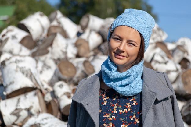 スタイリッシュな服を着た陽気な魅力的な女性(花柄のドレス、ニットの手作り帽子とコート)は微笑んで、自然を楽しみ、白樺の丸太の山に座っています。村の生活のコンセプト