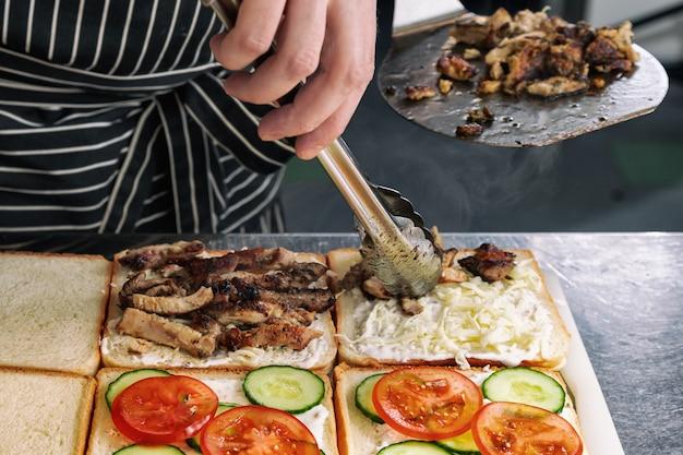 Крупный план приготовления вкусных бутербродов с мясом на гриле, майонезом, помидорами, сыром и огурцом