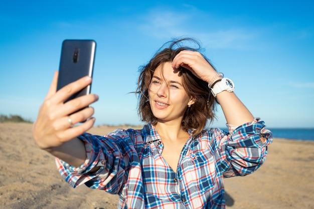 陽気な黒髪の女性は微笑んで、電話で自撮りを撮り、ビーチを散歩し、夏の日に明るい太陽を楽しんでいます。海とライブスタイルで夏休みのコンセプト
