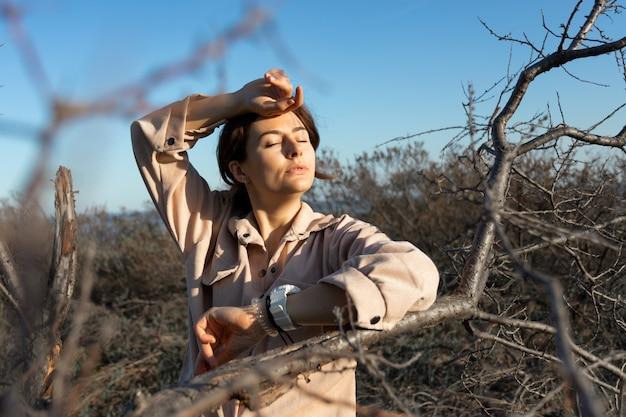 Романтичный портрет молодой женщины с вьющимися волосами в джинсах ретро очки против дерева, леса. творческий портрет женщины в природе. дизайн концепт-арт
