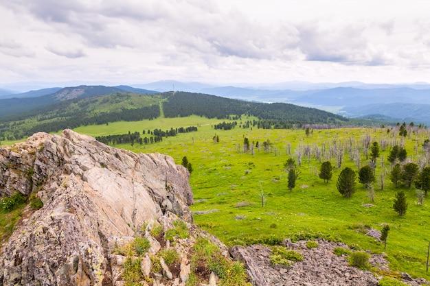 Летний пейзаж горы алтая чемальского района: высокие горы, покрытые сосной и кедром, покрытые облаками.