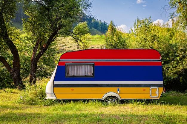 Автоприцеп, дом на колесах, окрашенный в государственный флаг армении, стоит на стоянке в гористой местности.