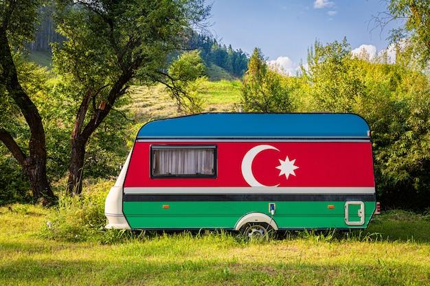 Автоприцеп, дом на колесах, окрашенный в государственный флаг азербайджана, стоит на стоянке в гористой местности.
