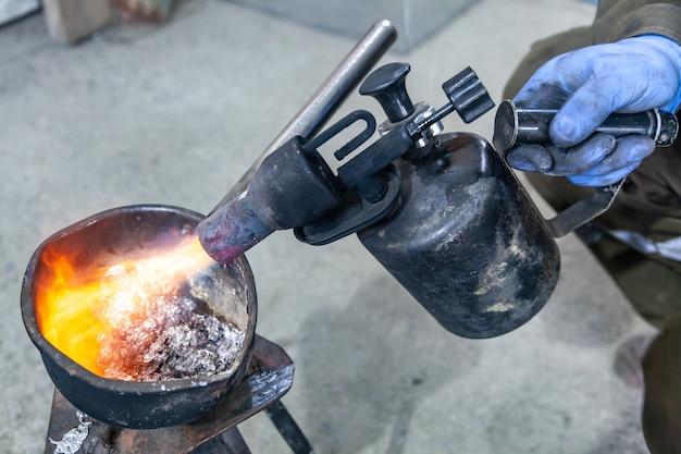 Профессиональный работник мужского пола, использующий газовую горелку, чтобы расплавить металлический свинец. крупный план газовой горелки с огнем, направленным прямо на расплавленный металл.