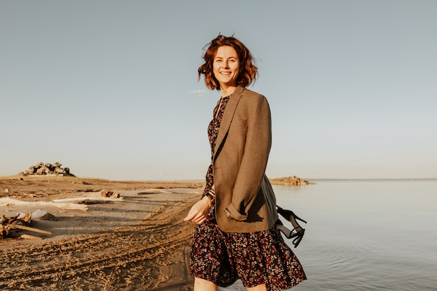 自然の中でポーズの女性。スタイリッシュな服の若い女性