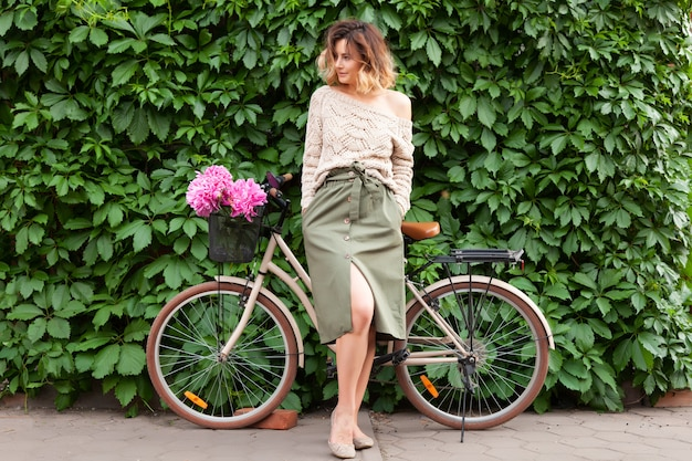 Красивая темноволосая женщина в свитере и бежевой юбке улыбается, позирует и стоит рядом с велосипедом.