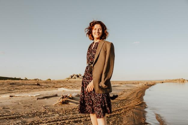 暗い髪の女性は笑顔でビーチを散歩し、夏の日に明るい太陽を楽しんでいます。海とライブスタイルで夏休みのコンセプト