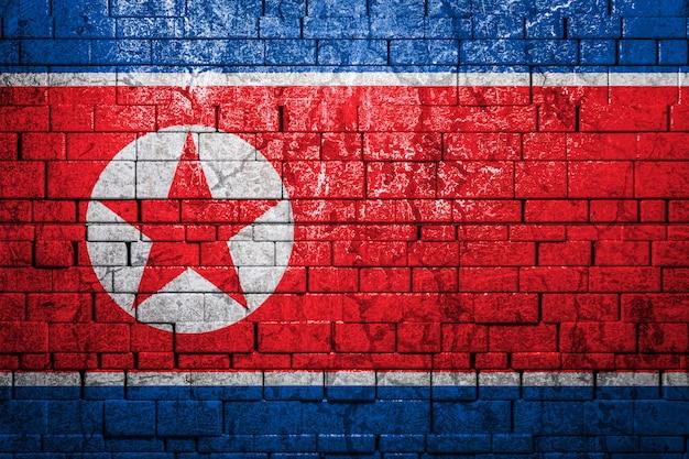 Национальный флаг северной кореи на кирпичной стене. концепция национальной гордости и символ страны.