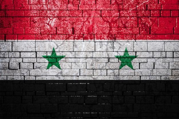 Национальный флаг сирии на кирпичной стене. концепция национальной гордости и символ страны.