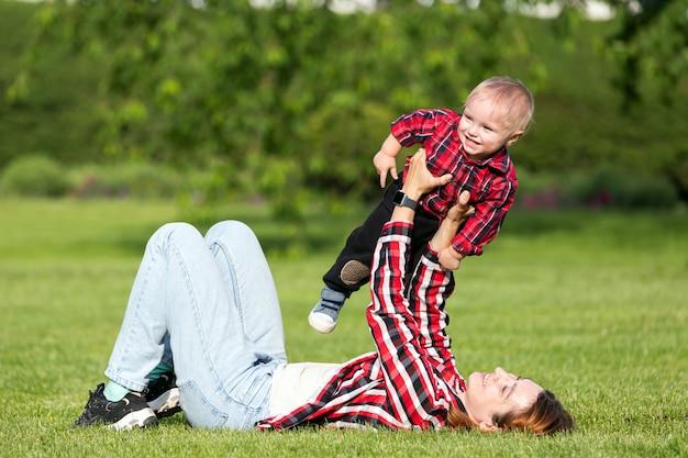 ママは小さな男の子の息子と遊ぶ、暖かい夏の日に公園で赤ちゃんを抱擁します。