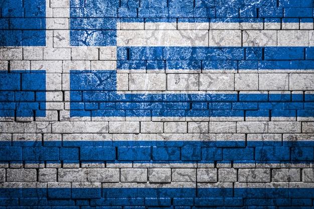 レンガ壁の背景にギリシャの国旗。