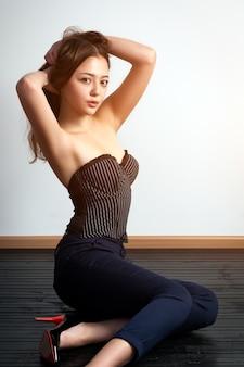 ブラックトップと古典的な黒のズボンのポーズでアジアの若い女性