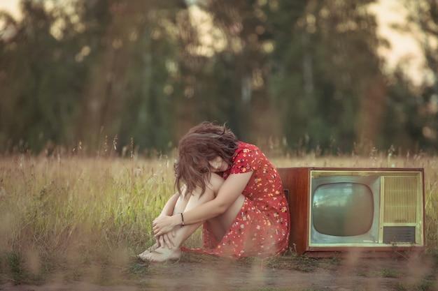 自然の中で古いレトロなテレビの近くに座っている赤いドレスを着た陰気な若い女性の大気の肖像画。