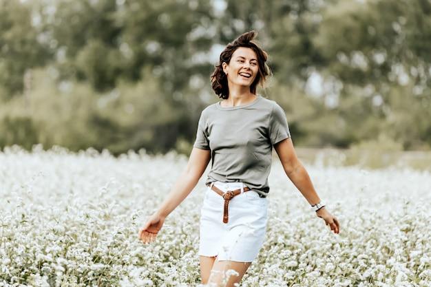 美しい女性の肖像画は白い花を持つフィールドを横切って走る