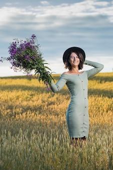 フィールドの上を歩いて紫色の花の花束と青いドレスの肖像画うれしそうな若い女性ブルネット。