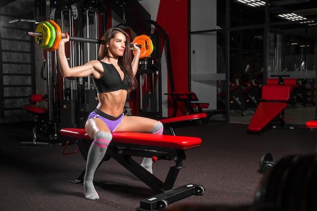Женщина делает упражнения в тренажерном зале
